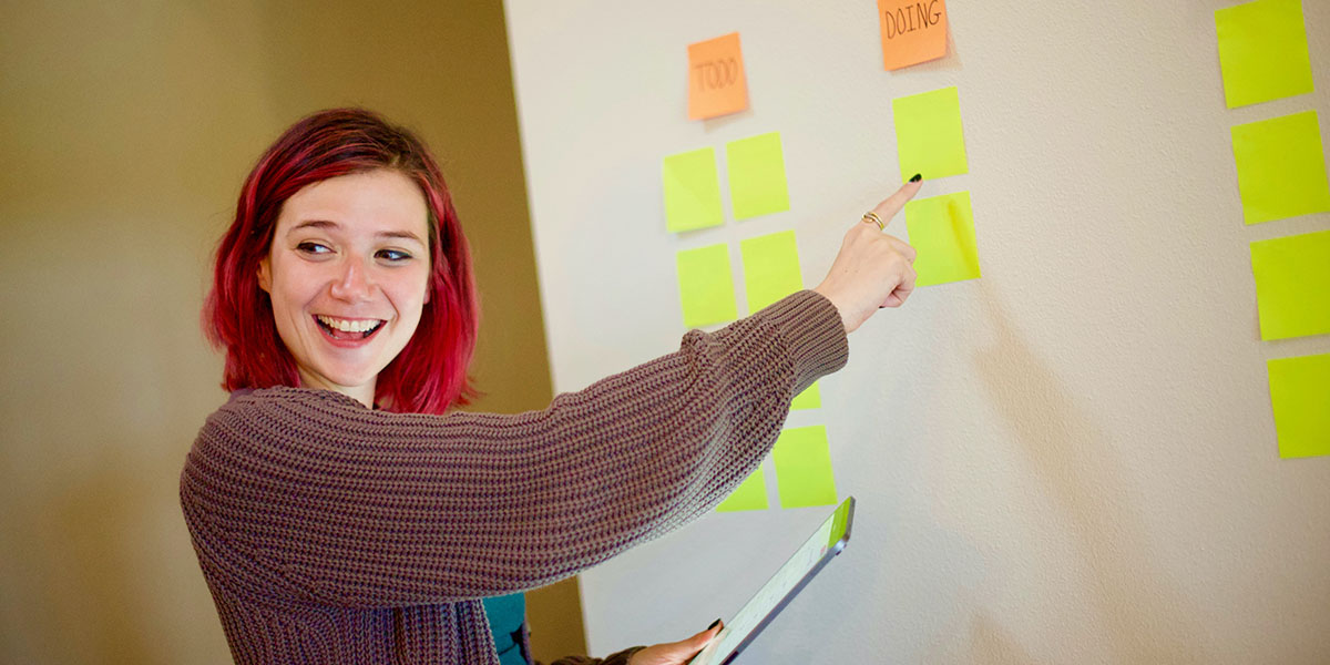 Kvinna visar agil metodik med post-it-lappar - en symbol för agil rekrytering